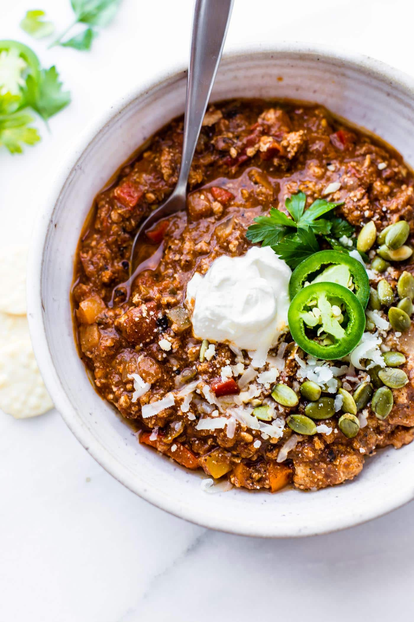 spoon in a bowl of thick turkey sweet potato chili topped with jalapenos and sour cream