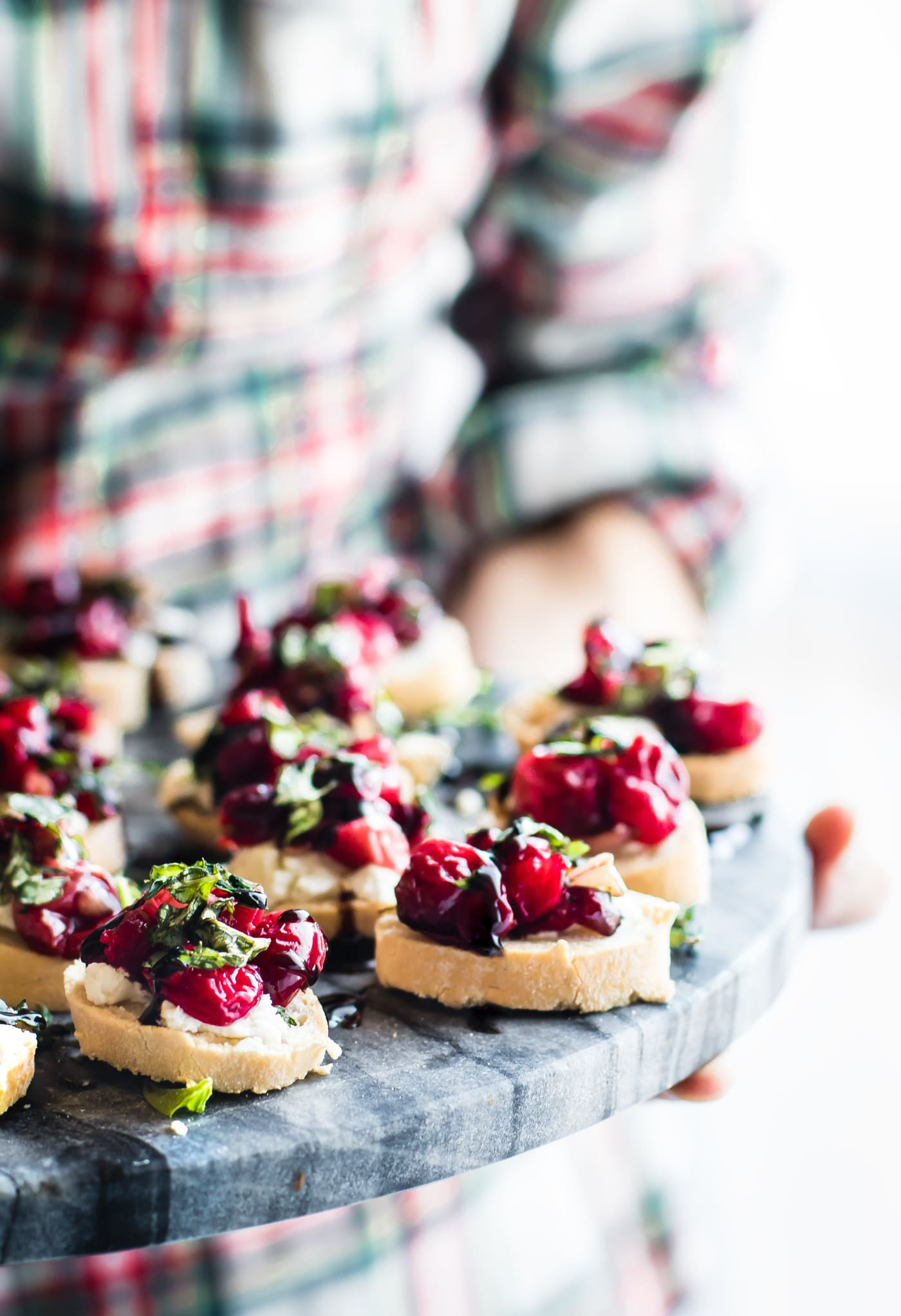 woman holding a platter of gluten free crostini appetizers