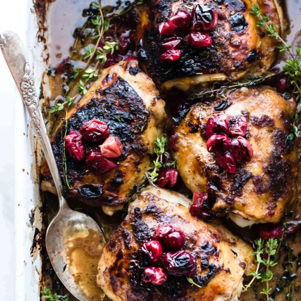 overhead photo: cranberry balsamic chicken on a baking sheet with serving spoon