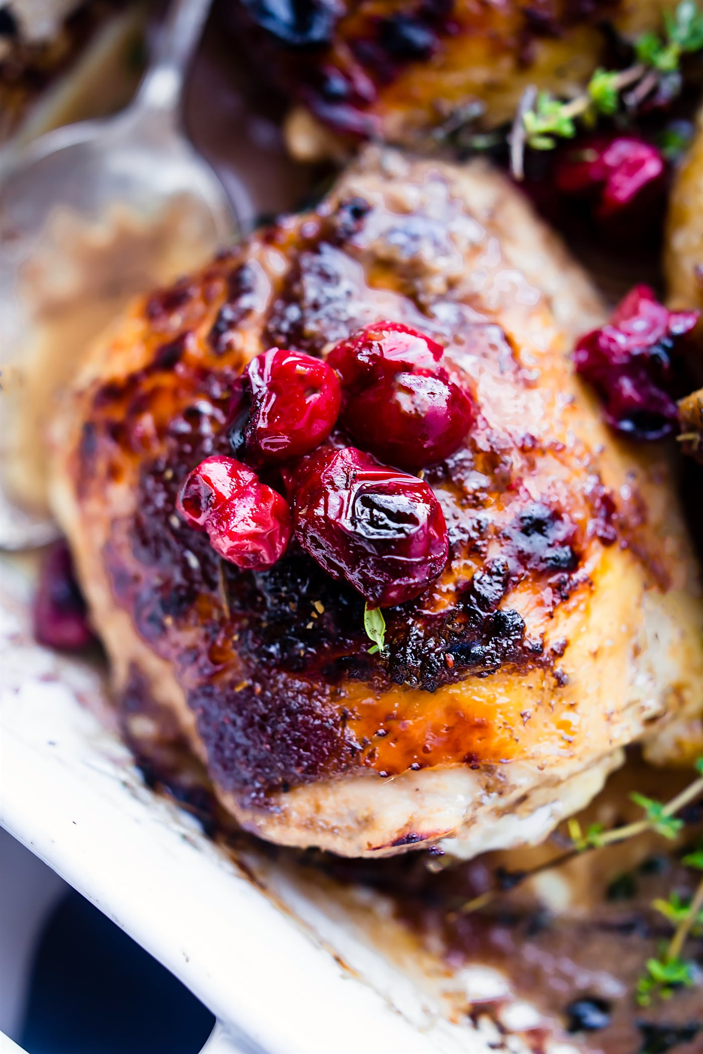 close up photo: bone-in oven roasted chicken thigh with balsamic marinade and roasted cranberries on top