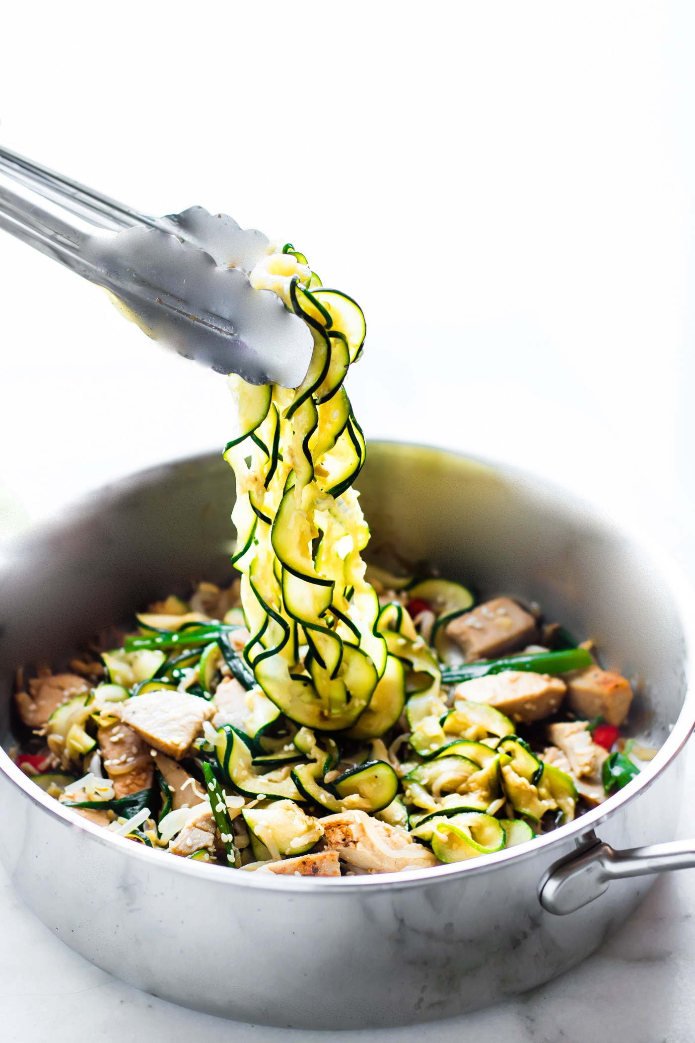 tossing zucchini noodles with turkey and veggies to make a healthy turkey and zucchini stir fry.