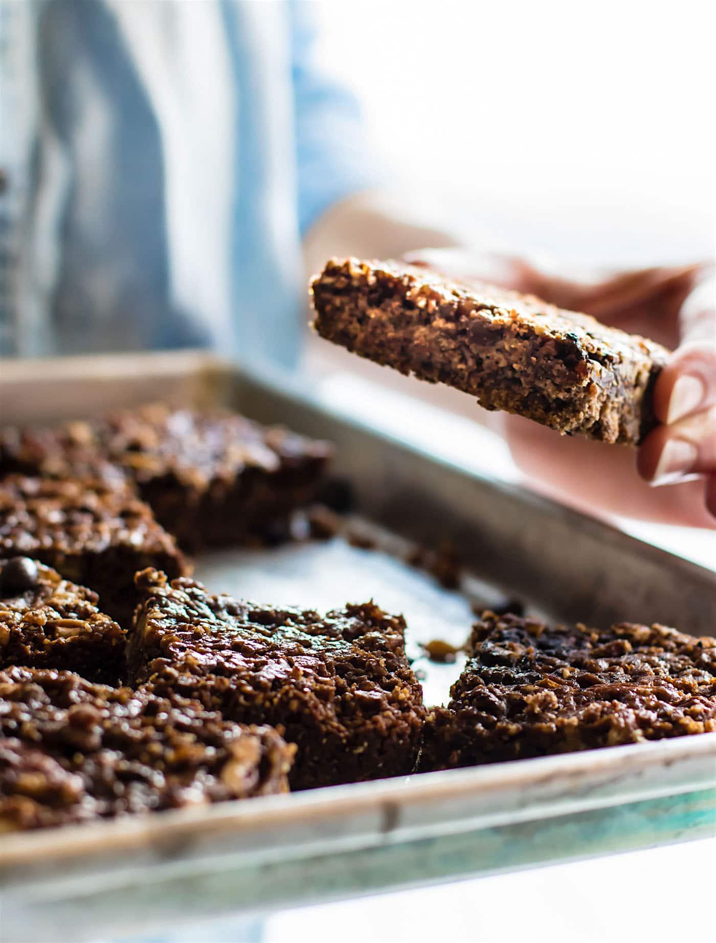 removing vegan pecan pie bars from a pan