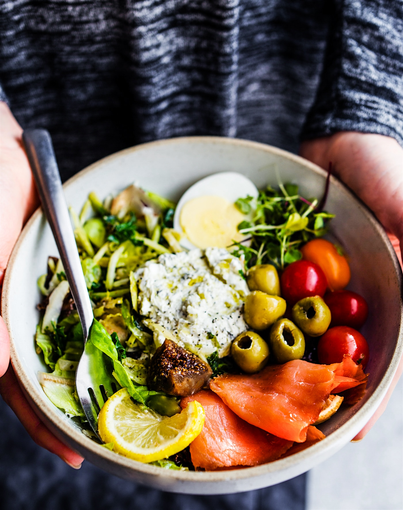 large bowl filled with warm greens salad with fish, hard boiled egg slices, olives and goat cheese