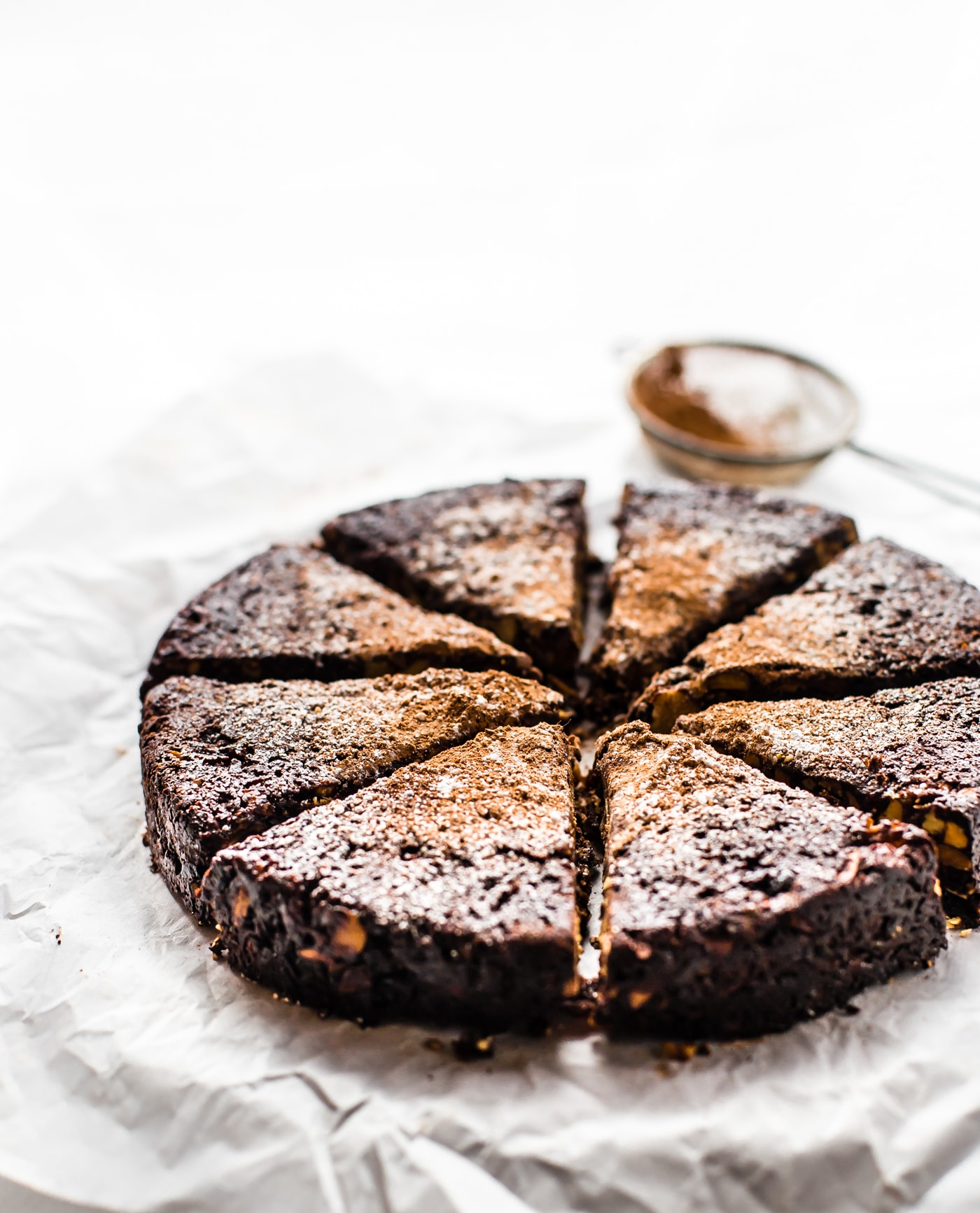 A chocolate Christmas cake cut into triangles, dusted with cocoa powder