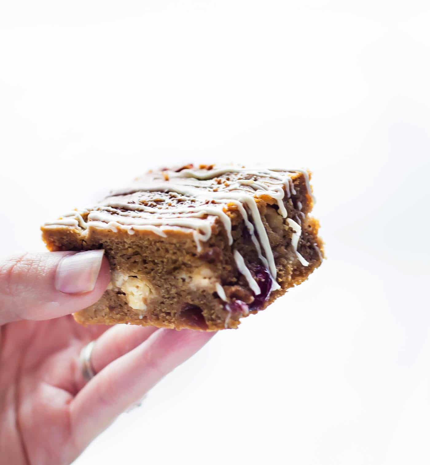 hand holding a cranberry white chocolate pumpkin bar