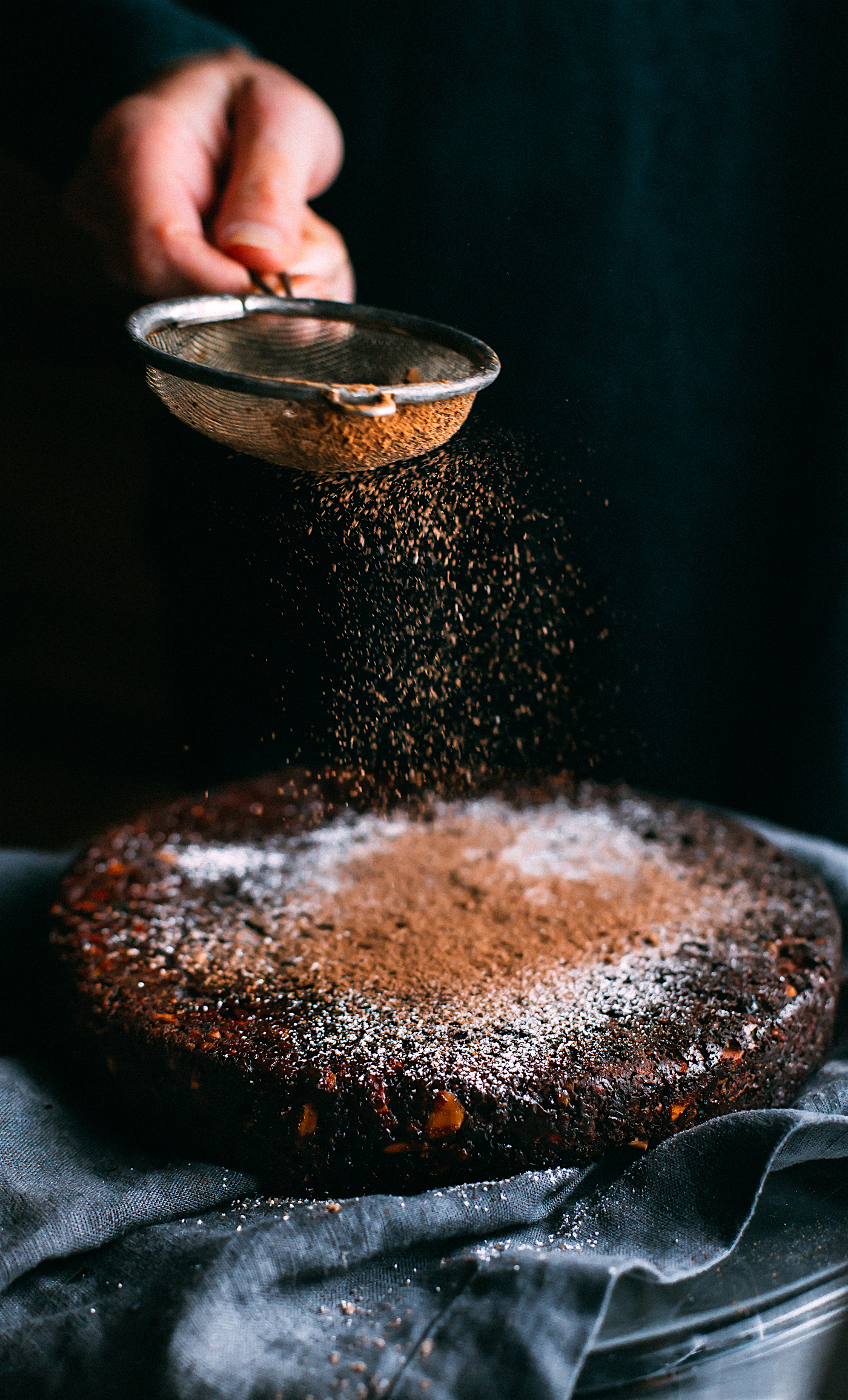 dusting cacao powder over a chocolate Christmas cake (Panforte)