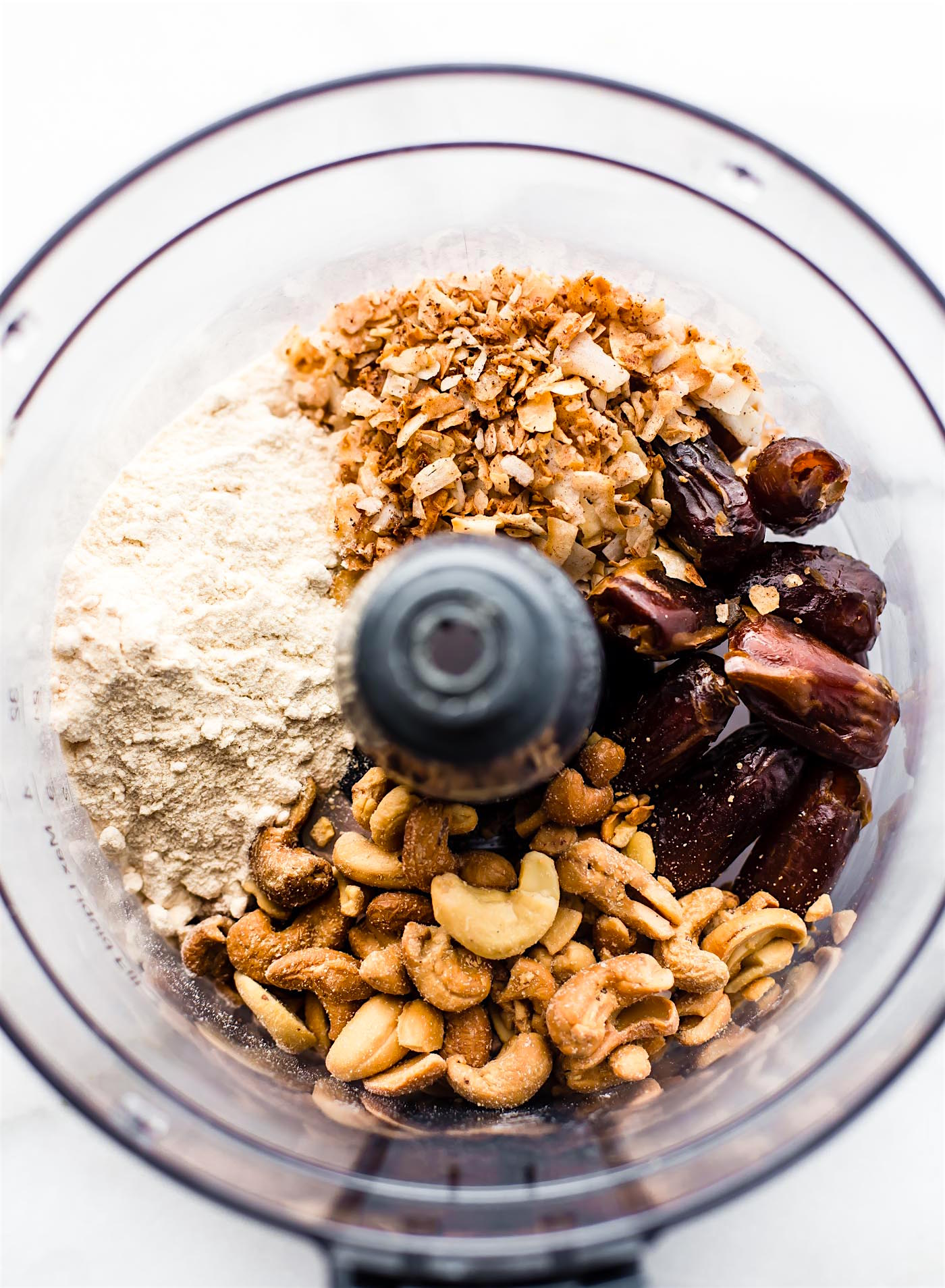 ingredients in a food processor to make healthy bliss balls with cinnamon toasted coconut and cashews