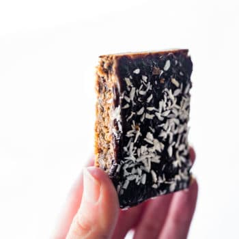 woman's hand holding up a Paleo Almond Butter Jelly Energy Bar