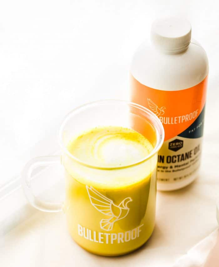 """Boost your health with a cold busting vegan orange turmeric tea latte! This caffeine free bulletproof """"Golden Milk"""" tea latte is rich in Vitamin C, healthy fats, and anti-inflammatory properties. #goldenmilk #latte #vegan #bulletproof #paleo"""