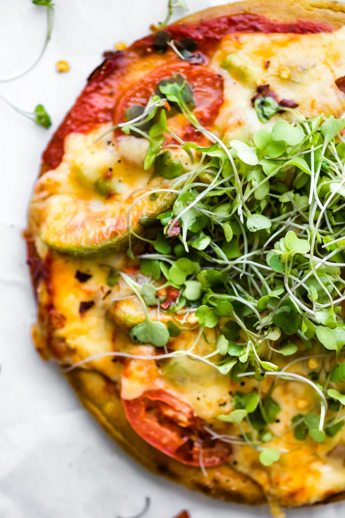 Avocado Tomato Gouda Socca Pizza recipe to love! A grain free, gluten free Avocado Tomato Gouda Socca Pizza made with chickpea flour and topped with Avocado, Gouda, Tomato, and Greens! Seriously easy to make, egg free, vegan option, OMG delicious!