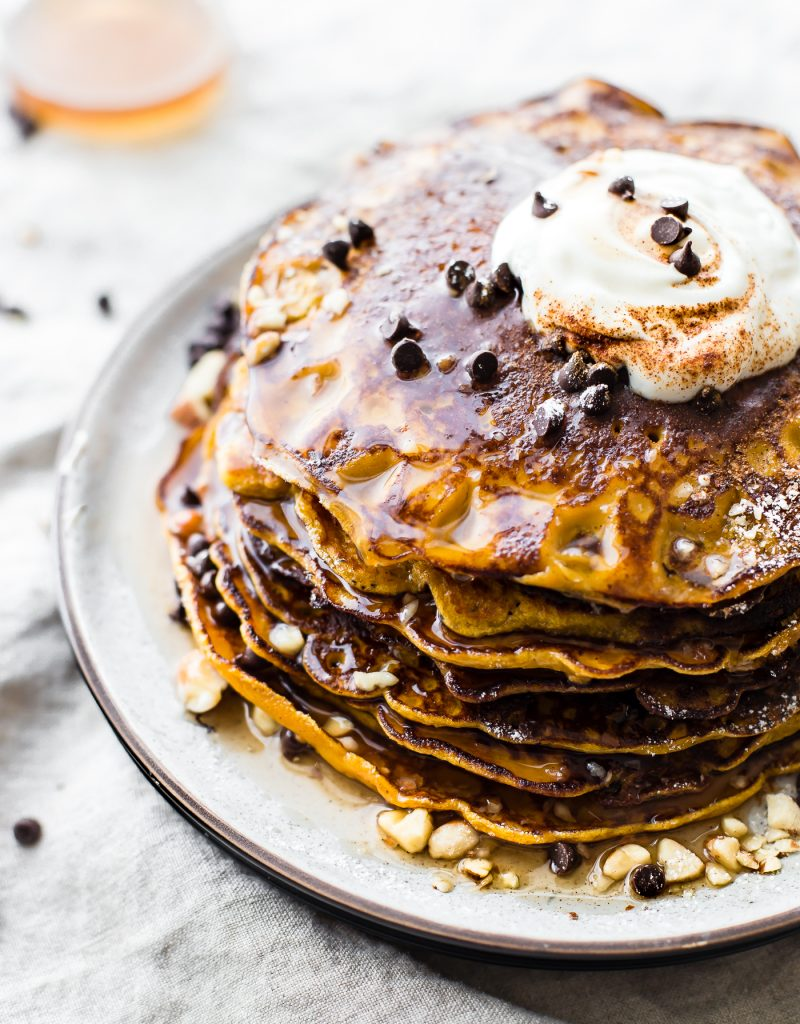 stack of Flourless Carrot Cake Yogurt Pancakes with syrup and mini chocolate chips