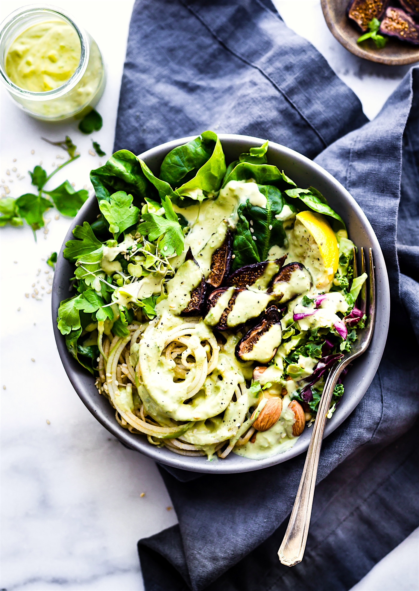 Quick and Easy Green Goddess Fig Nourish Bowls! These plant powered nourish bowls are packed with super greens, healthy fats, nature's candy (Fruit and Figs), and topped with homemade green goddess dressing. They will fill you up and nourish you all at once. Paleo, Vegan, and Whole 30 friendly!