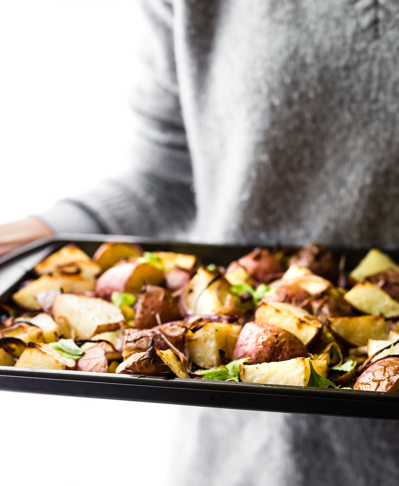 Holding a pan of roasted Leek and Potato! This Vegetable Pan Roast is packed with Seasonal Leek, Potato, and Steamed Spinach Greens! A flavorful, healthy, and easy to make side dish you can make all in one pan! A paleo/vegan Spring recipe perfect for any gathering. Whole 30 friendly!