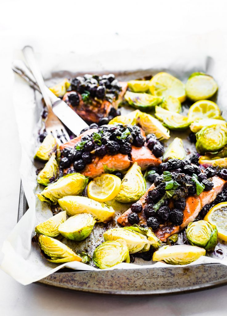 One pan Paleo SUPERFOOD Baked Salmon is ready in 20 minutes and packed full of nutrients. A nourishing, whole 30 friendly, flavorful meal! Salmon baked with a zippy basil blueberry balsamic topping and crispy Brüssels sprouts!