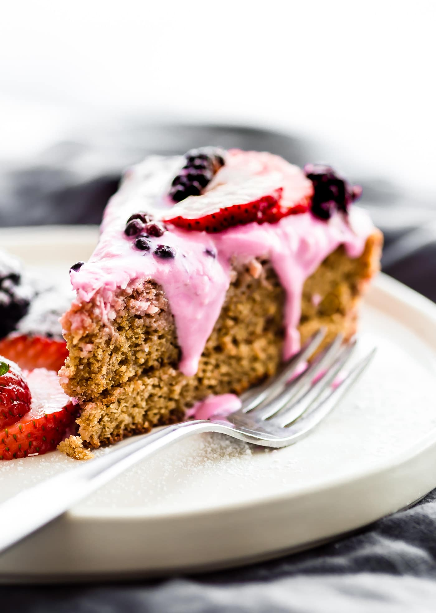 This berry yogurt frosted flourless cake is incredibly light and fluffy. A flourless cake made simply from egg whites, almond flour, and berries. Topped with a strawberry greek yogurt frosting. It's the perfect light dessert for summer!