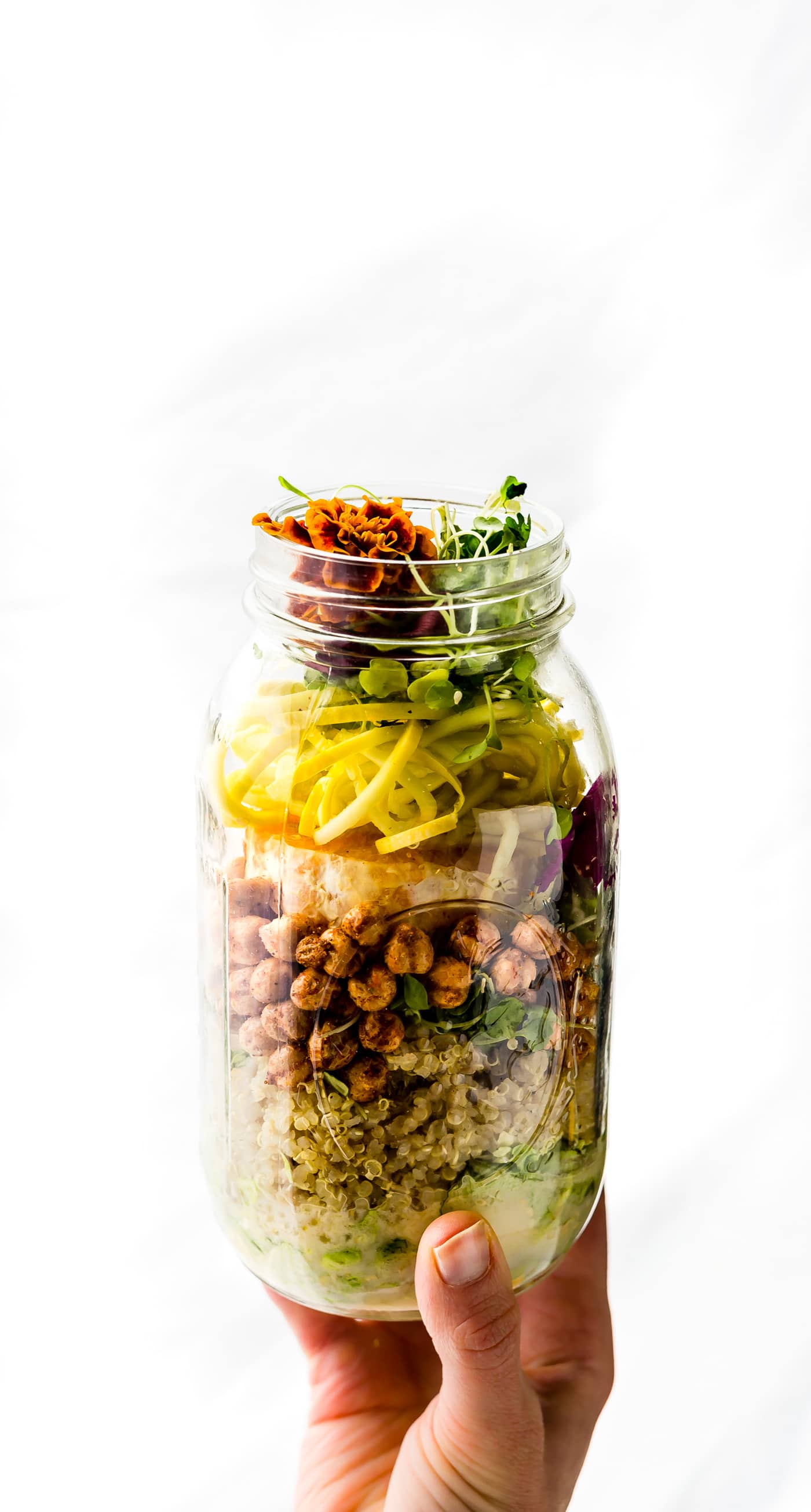 Mason jar salads are healthy, portable salads, picnic ready and packed with nourishment! This vegetarian Mason Jar Salad will keep you fueled and energized all day! Seasonal vegetables, roasted chickpeas, and a homemade sesame yogurt dressing make for a perfectly balanced lunch at home or on the go.