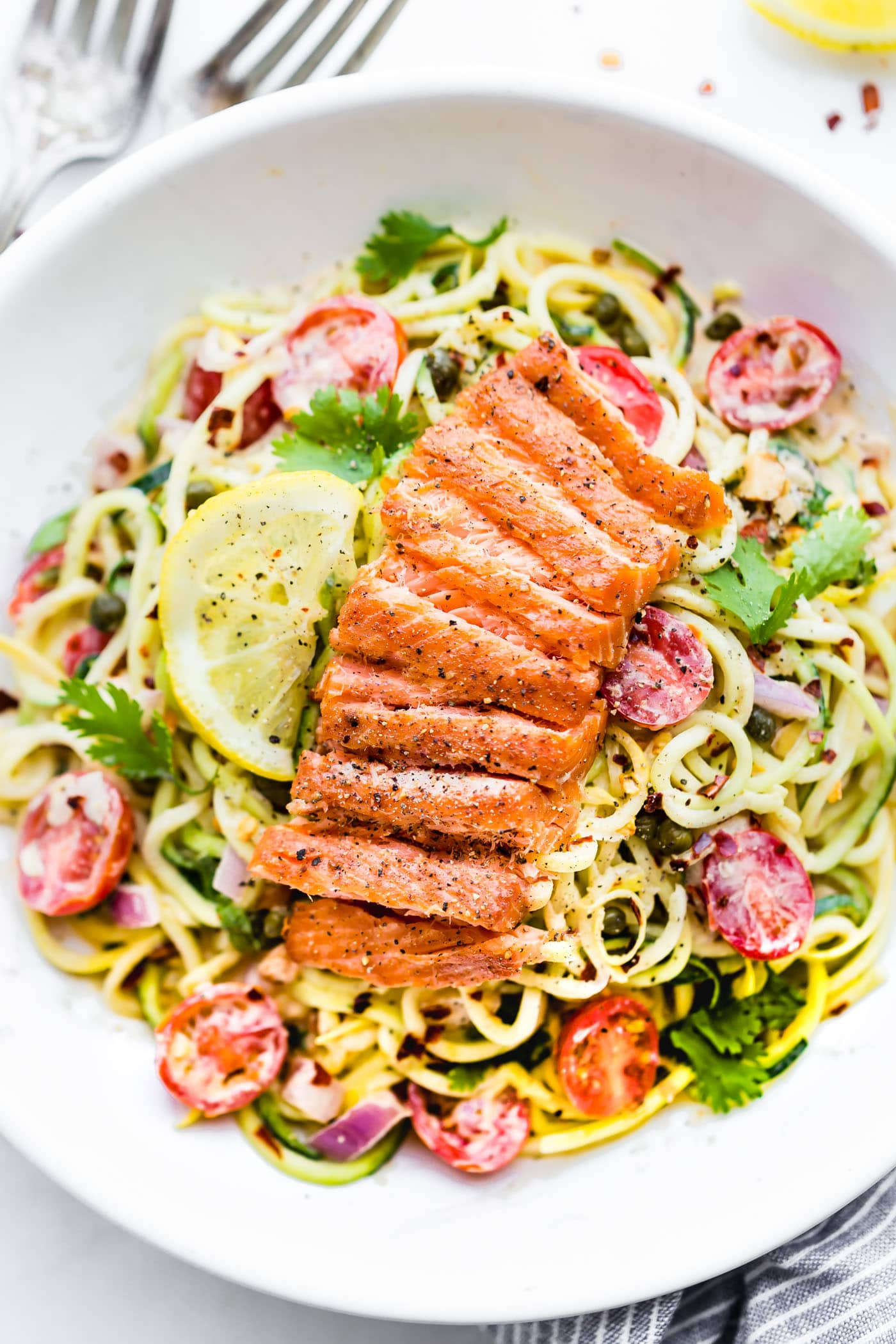 Cajun Smoked Salmon Pasta Salad served in a white bowl with cilantro and a lemon wedge as garnish