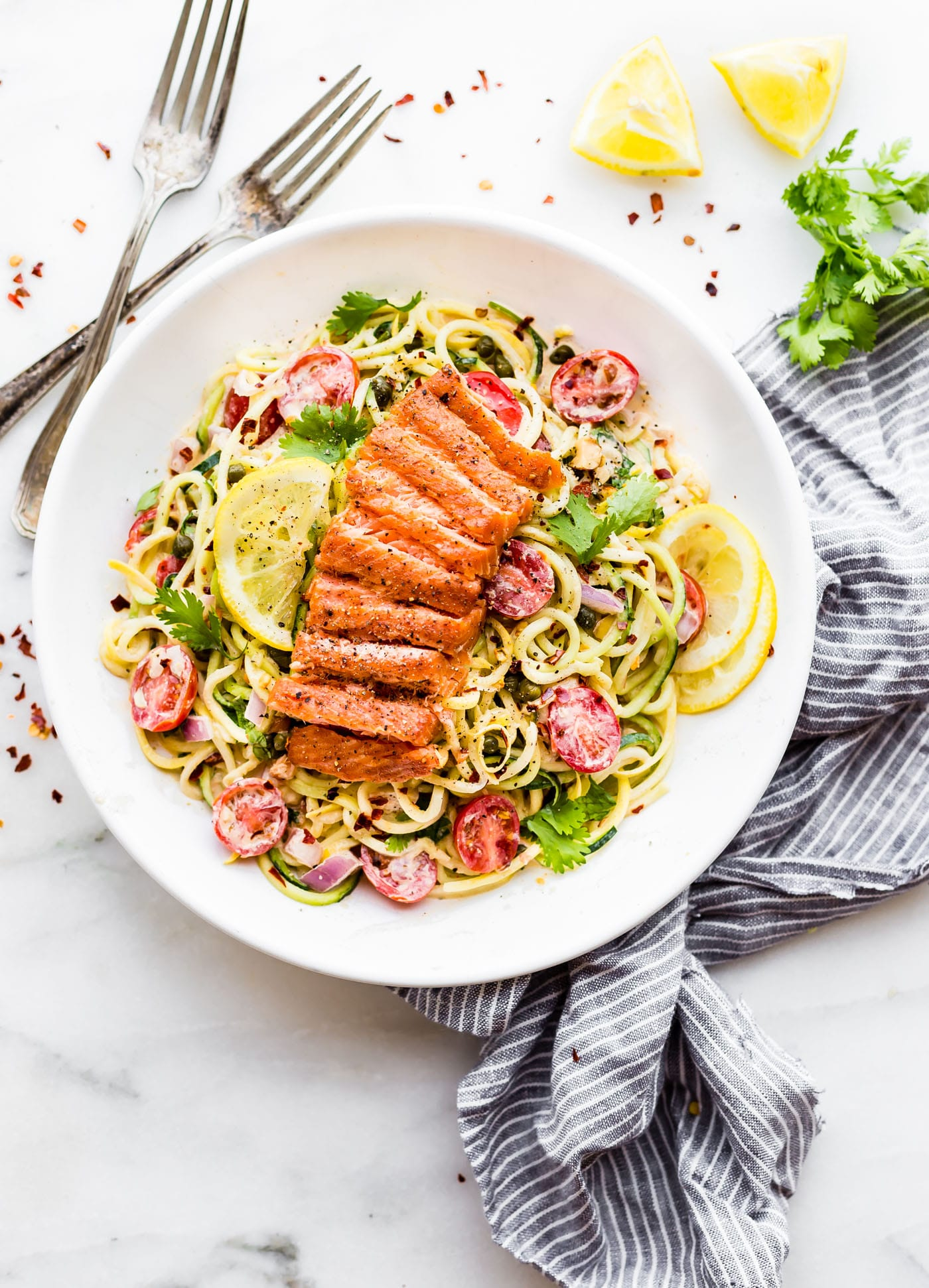 Smoked Salmon Zucchini Noodles Salad makes for a perfect no cook meal! A zippy cajun sauce tossed in chopped vegetables and zucchini noodles then topped with peppery smoked salmon. Paleo and Real food deliciousness!