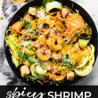 Spicy shrimpCaesar Spinach salad in bowl with lemons and dressing on side