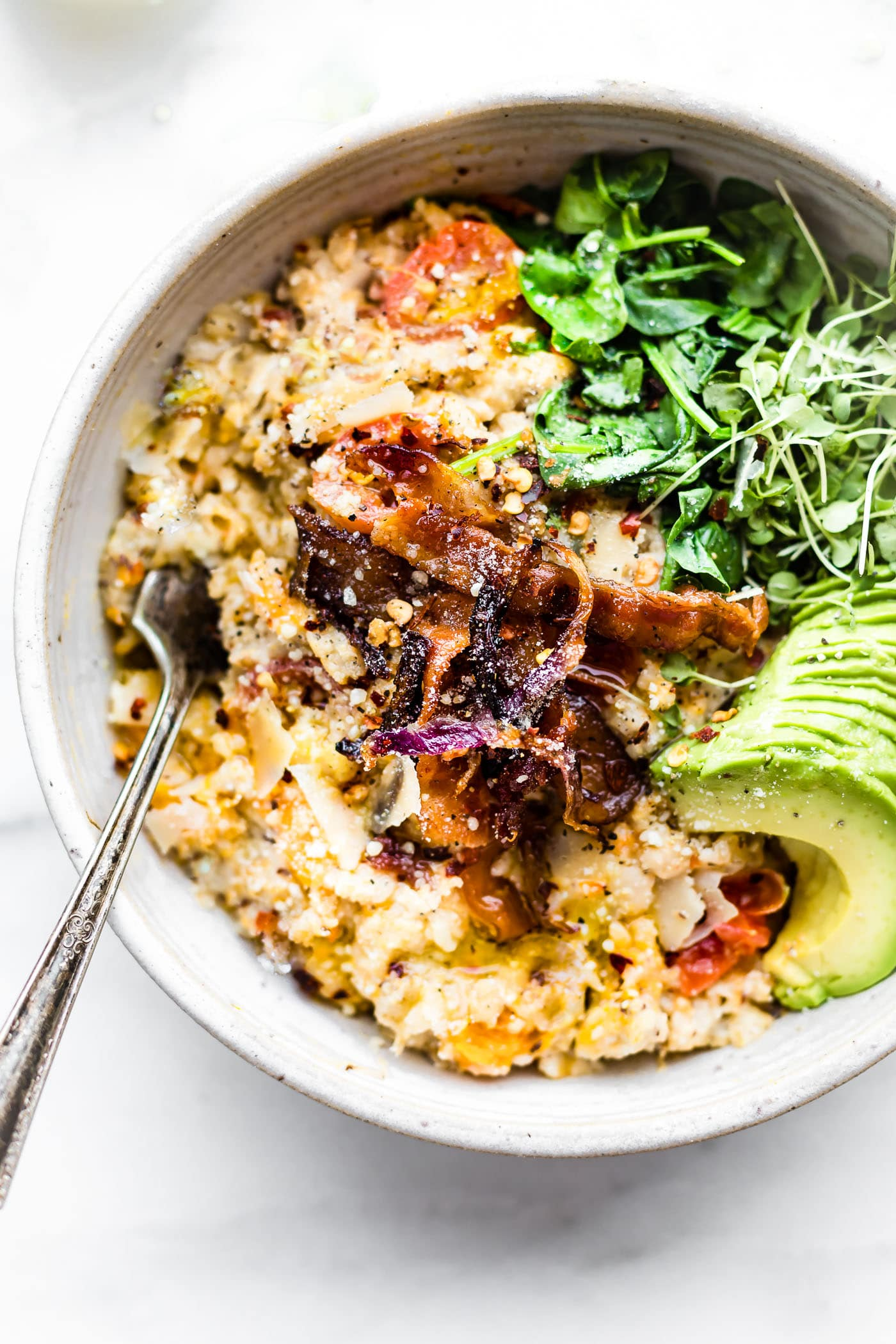 This Savory slow cooker oatmeal with crispy bacon will make you jump out of bed! A savory spin to your regular sweet oatmeal and total crowd pleaser dish, which is perfect for busy mornings! A Slow cooker oatmeal made with the addition butternut squash, garlic, herbs, parmesan cheese, and topped with crispy bacon and avocado. An easy to make well-rounded healthy meal for any time of day. Dairy free option
