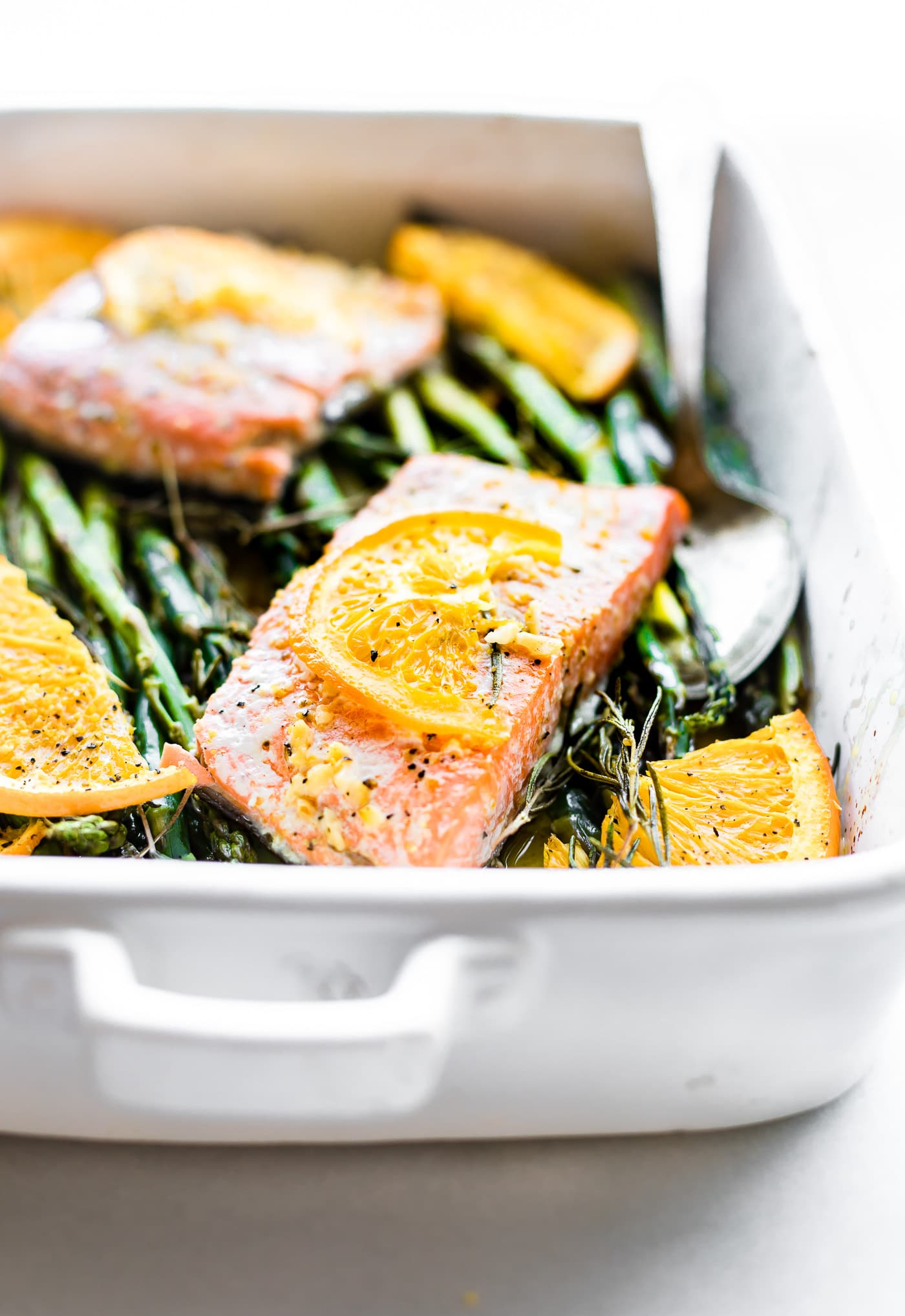 This Rosemary Citrus Baked salmon is a healthy one pan meal ready in 20 minutes.  Fresh Rosemary, orange juice, lemon, veggies, sockeye salmon, olive oil, and spices. A deliciously nourishing meal that's simple to make. #onepanmeal #healthy