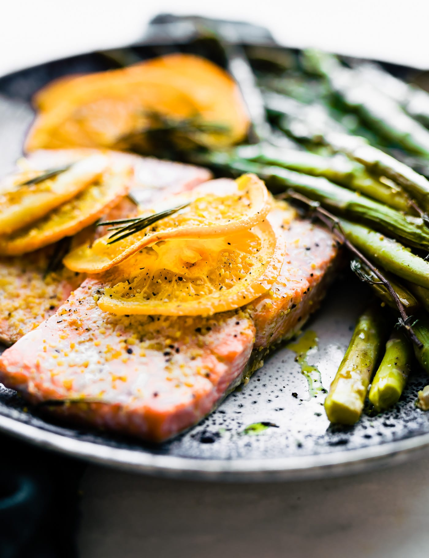 This Rosemary Citrus Baked salmon is a healthy one pan meal ready in 20 minutes.  Fresh Rosemary, orange juice, lemon, veggies, sockeye salmon, olive oil, and spices. A deliciously nourishing meal that's simple to make. #paleo #whole30
