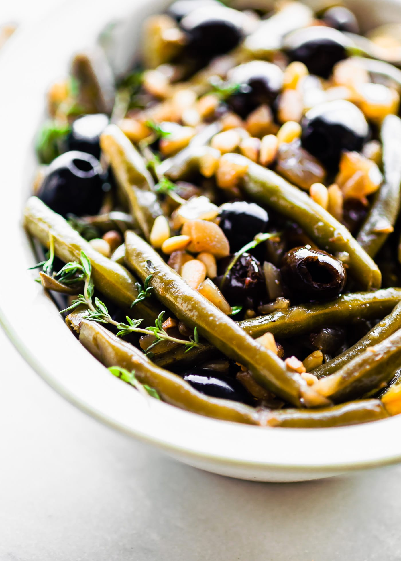An easy slow cooked side dish to add to your table. Balsamic braised green Beans. Fresh green beans, thyme, balsamic vinegar, olive-oil, black olives, onion & toasted pine nuts. Paleo, vegan friendly.