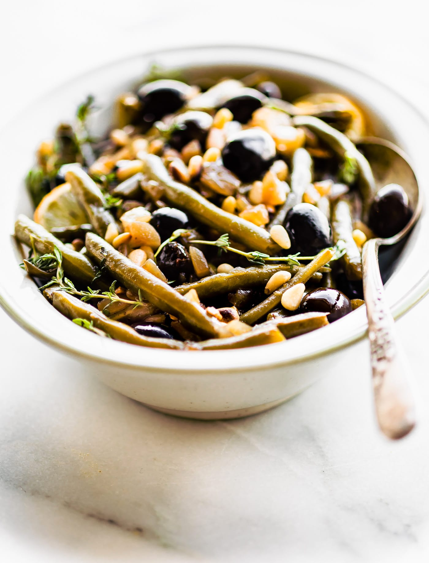 Balsamic Olive-Oil braised green Beans with a quick, easy, and healthy side dish. For this braised green beans recipe, fresh green beans are seasoned with thyme, then braised with balsamic vinegar, olive-oil, black olives, and topped with toasted pine nuts. Paleo, whole 30 and vegan friendly.