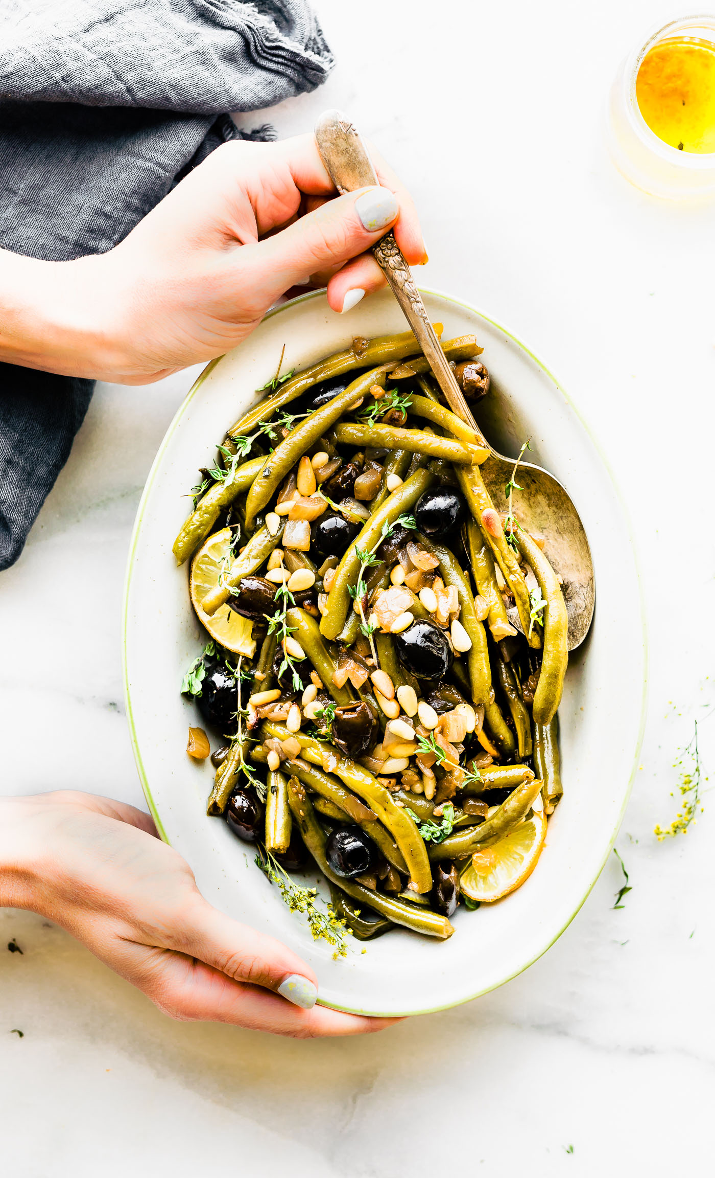 Balsamic braised green Beans are a quick healthy side dish. Fresh green beans, thyme, balsamic vinegar, olive-oil, black olives, onion & toasted pine nuts. Paleo, vegan friendly.