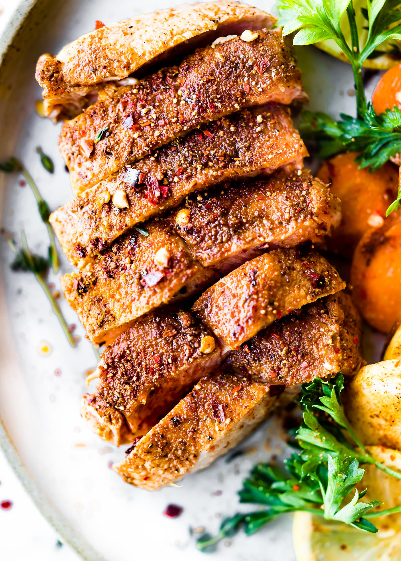 ThisCinnamon Chipotle Baked Pork Chops with parsnips and carrots makes an easy one pan meal. Boneless baked pork chops rubbed in a sweet smokey seasoning, roasted veggies, and herbs to garnish. A paleo meal ready in 30 minutes.