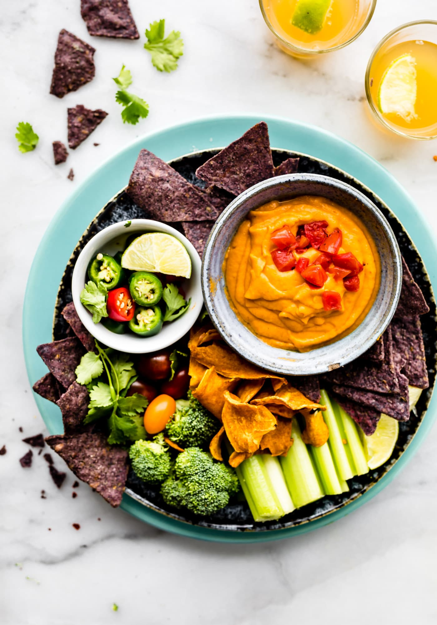 Vegan Salsa Con Queso on a platter with raw vegetables for dipping