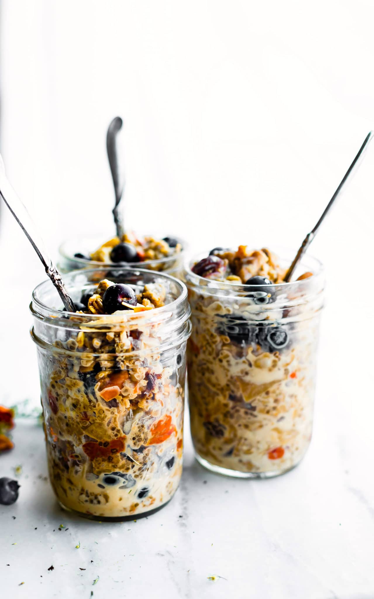 superood instatn pot oatmeal in mason jars topped with berries and served with spoons sticking out of the top