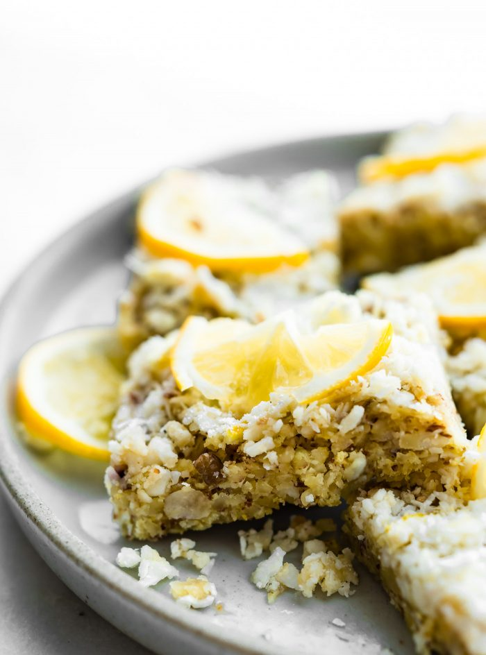 EASY LEMON COCONUT PALEO ENERGY BARS that are lower in sugar and NO BAKING required. These zesty energy bars are made with just a few simple ingredients; ground nuts, lemon zest, unsweetened coconut, and just a tiny bit of unrefined natural sugar. Perfect for the carb conscious snacker. Vegan and keto friendly.