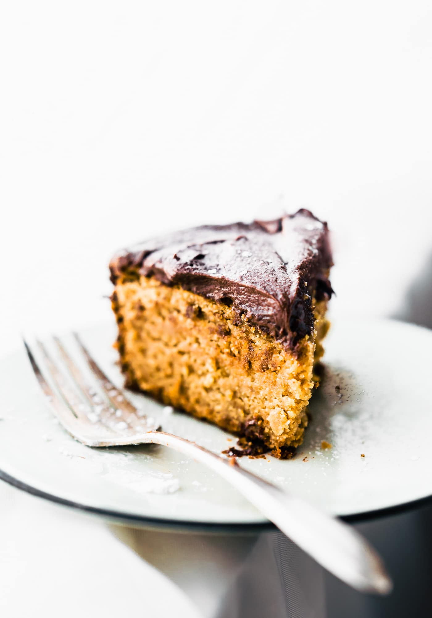 Slice of Vegan White Cake with Chocolate Coconut Cream Frosting on a plate. (paleo)