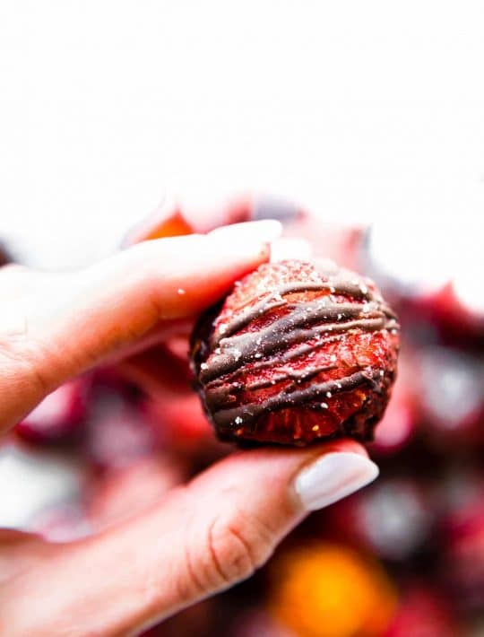 woman holding a fudgy strawberry chocolate brownie ball in her fingers