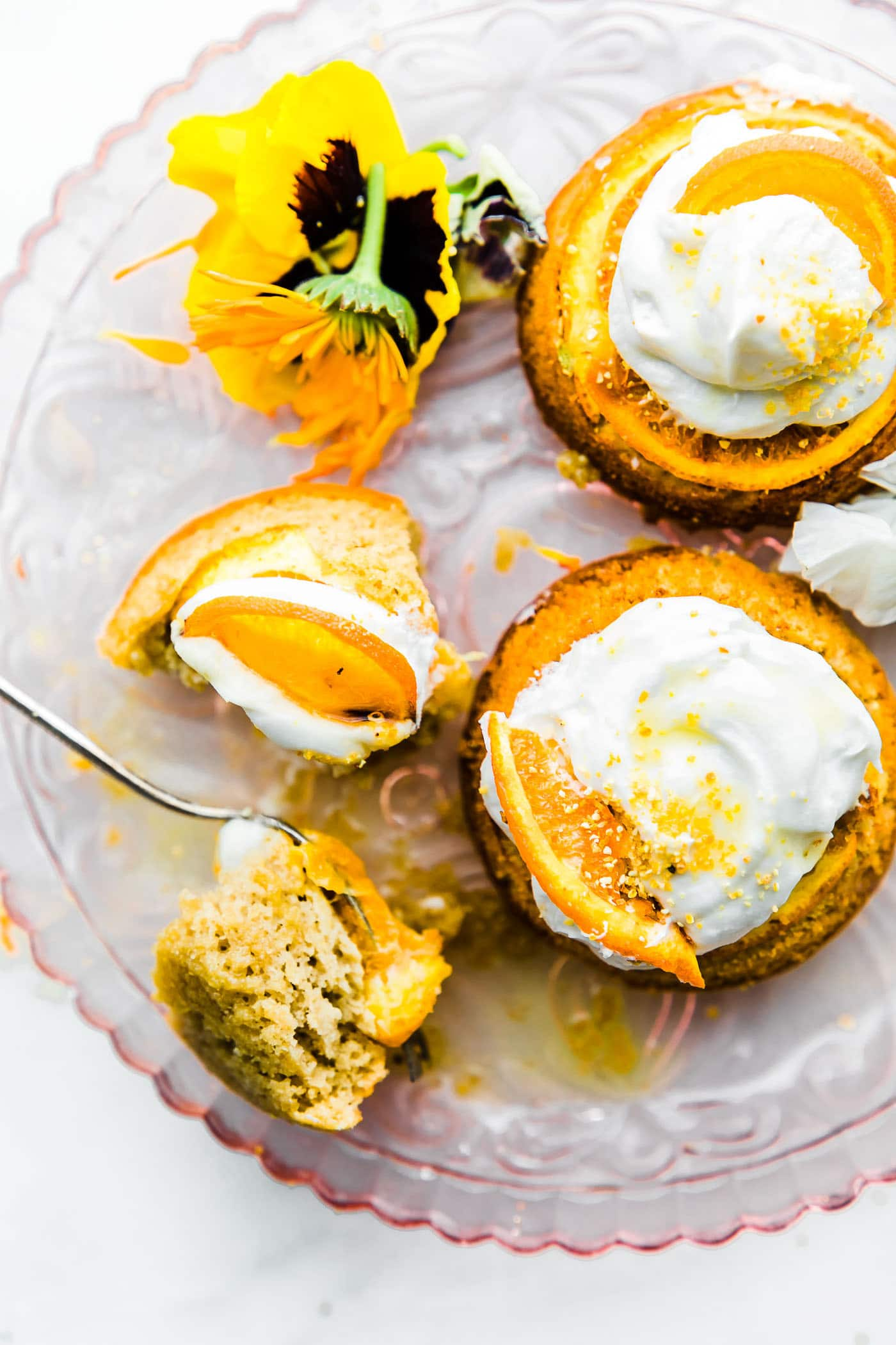 Orange Mini Paleo Upside cake (cakes) with cream on plate with fork.