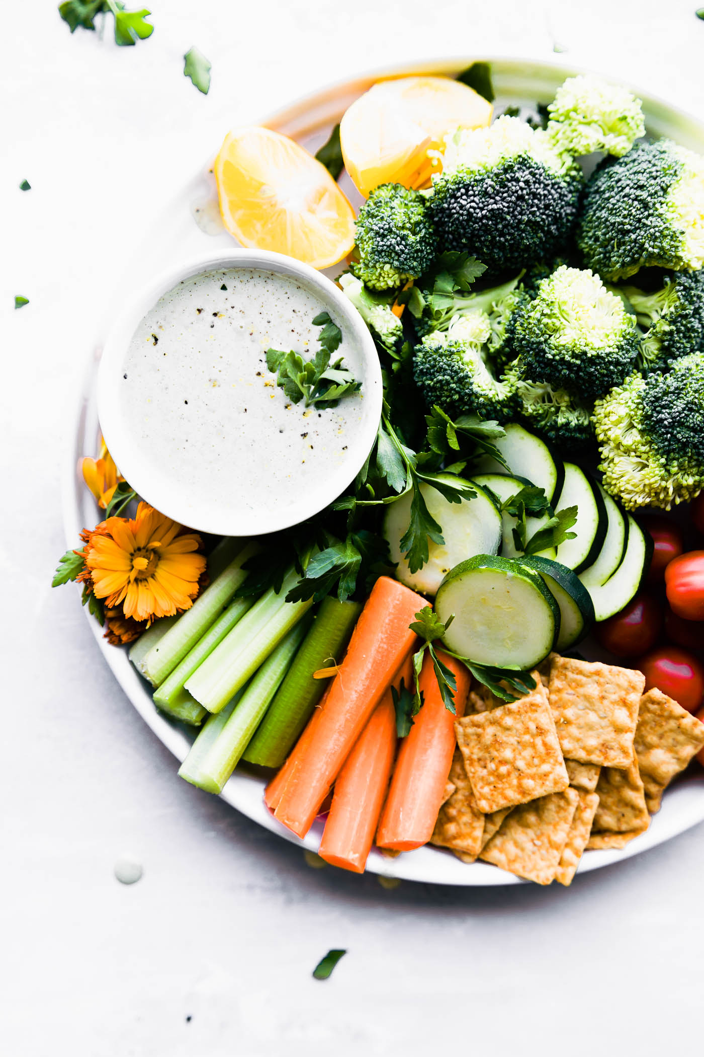 "Quick Homemade Vegan ranch dressing (aka ""Rancher's Dressing""). Vegan, paleo, and Whole 30 friendly, this creamy dairy-free ranch dressing is made from blended cashews, nut milk, herbs, and oil. We're serving it up in a veggie packed snack platter that's perfect for any occasion. #vegan #paleo #ranch"