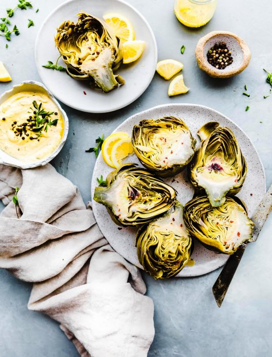 steamed artichokes on a plate with Mediterranean aioli