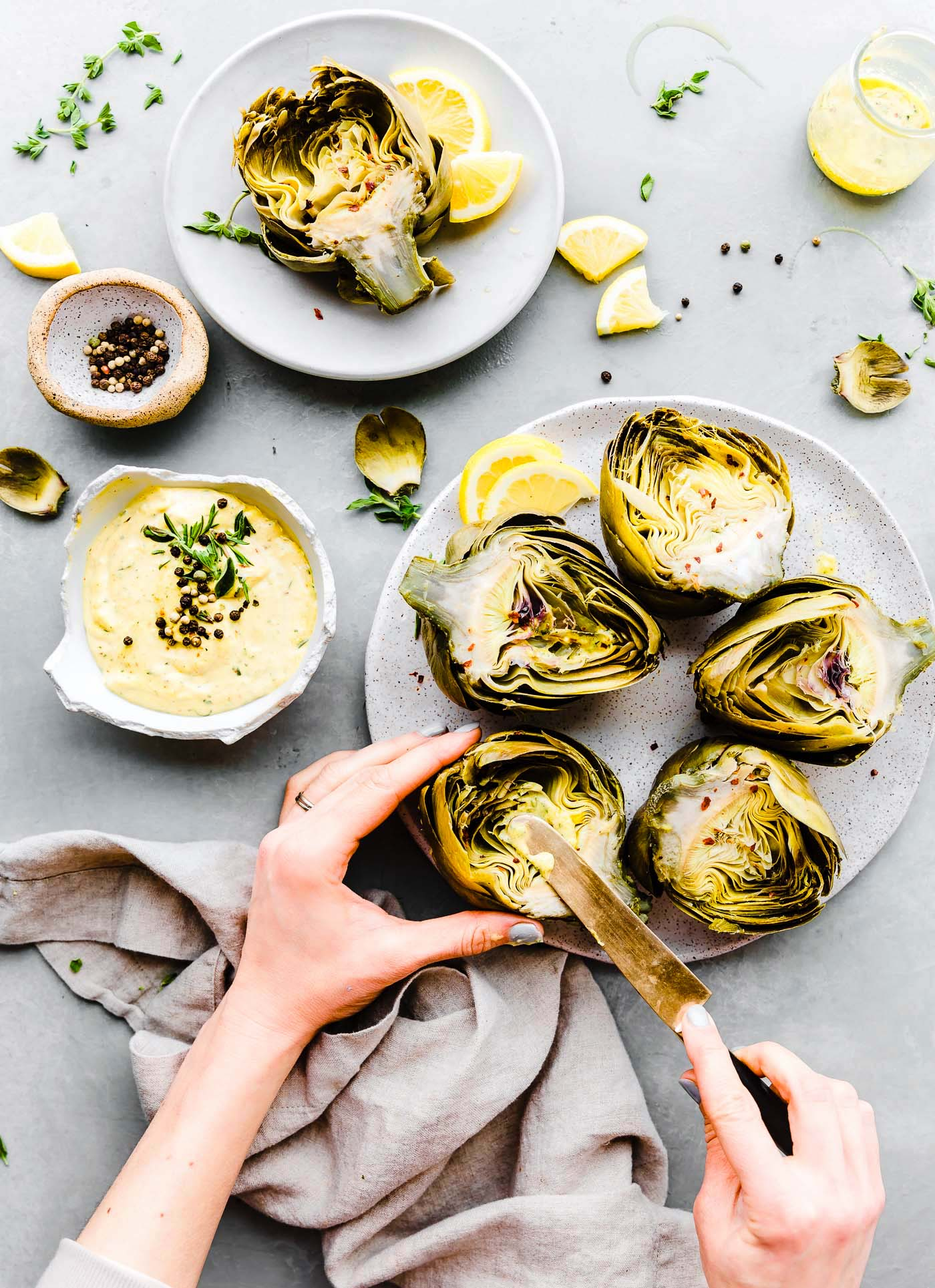 spreading aioli onto steamed artichokes