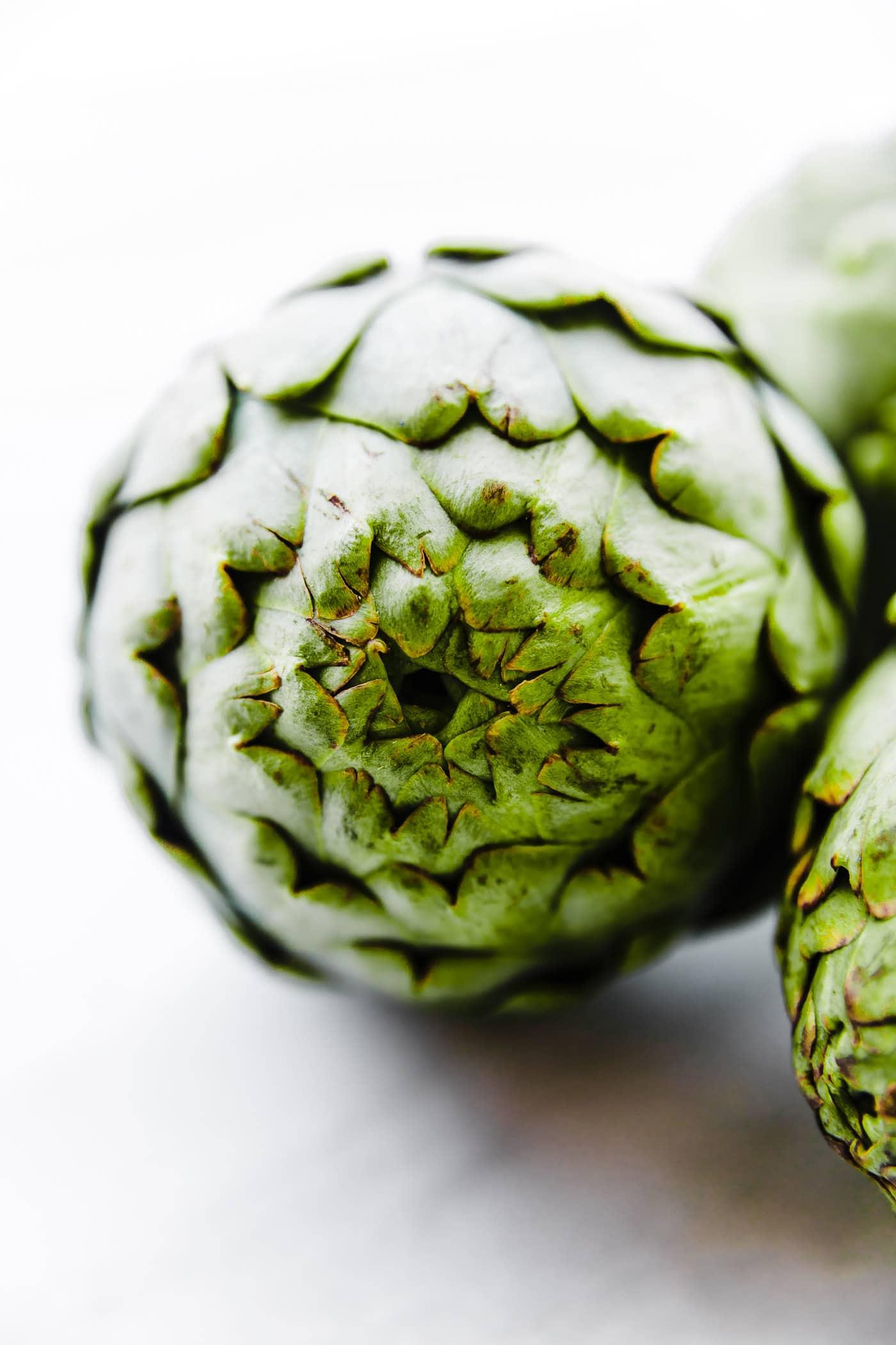 A close up image of a raw artichoke.