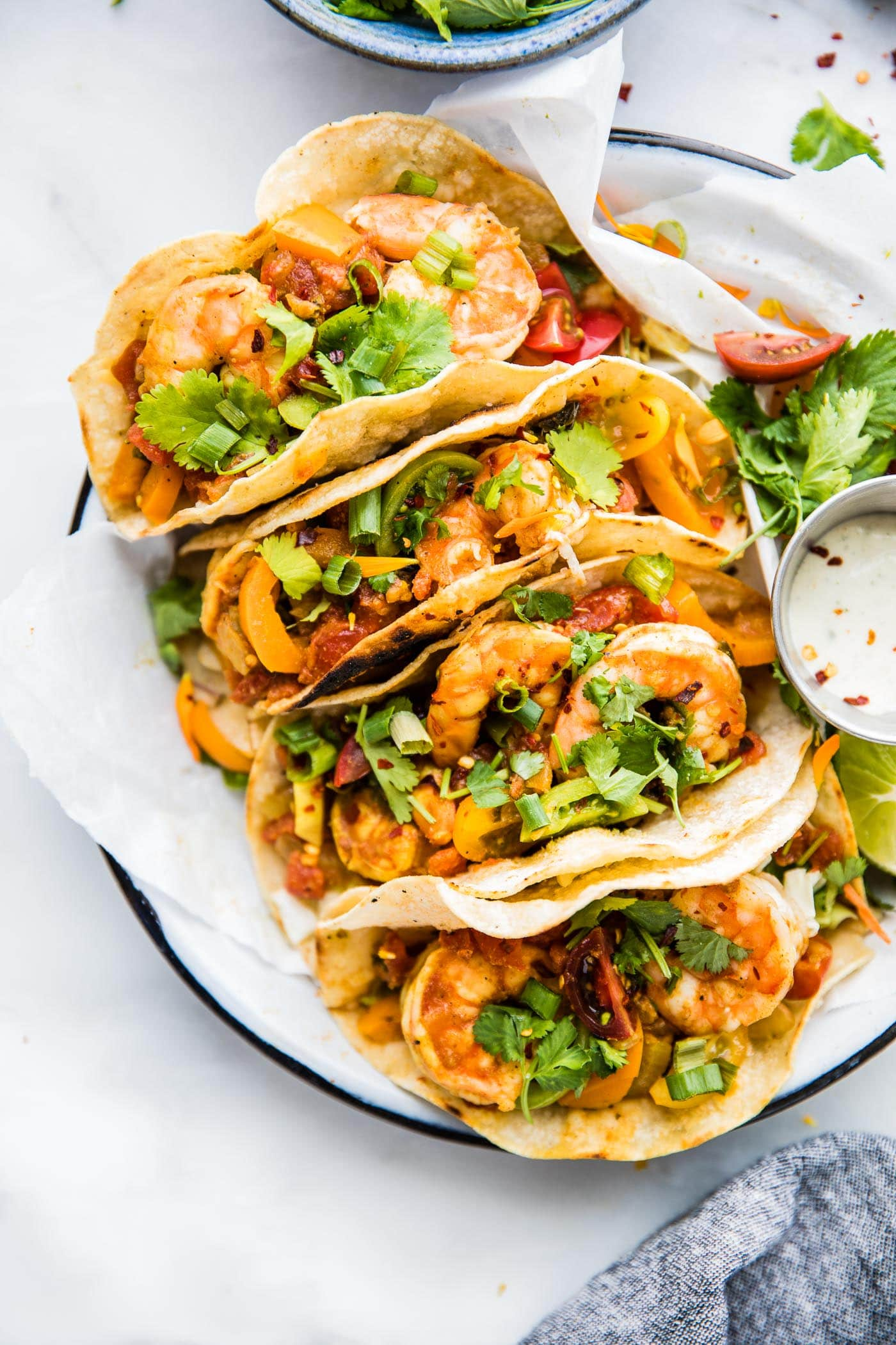 crock pot tacos with shrimp and toppings on a plate