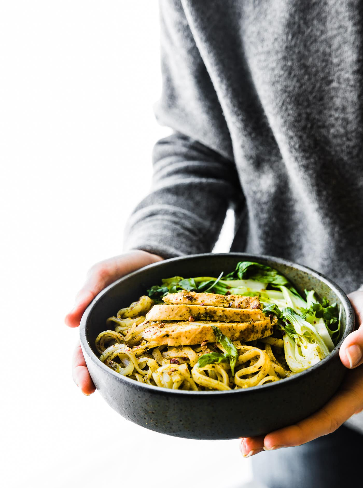 woman holding bowl of gluten free stir fry noodles with grilled chicken