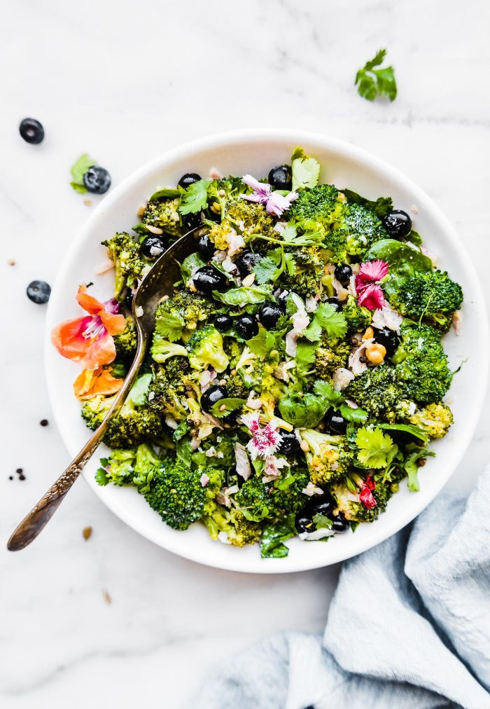 detox broccoli salad in white bowl with serving spoon