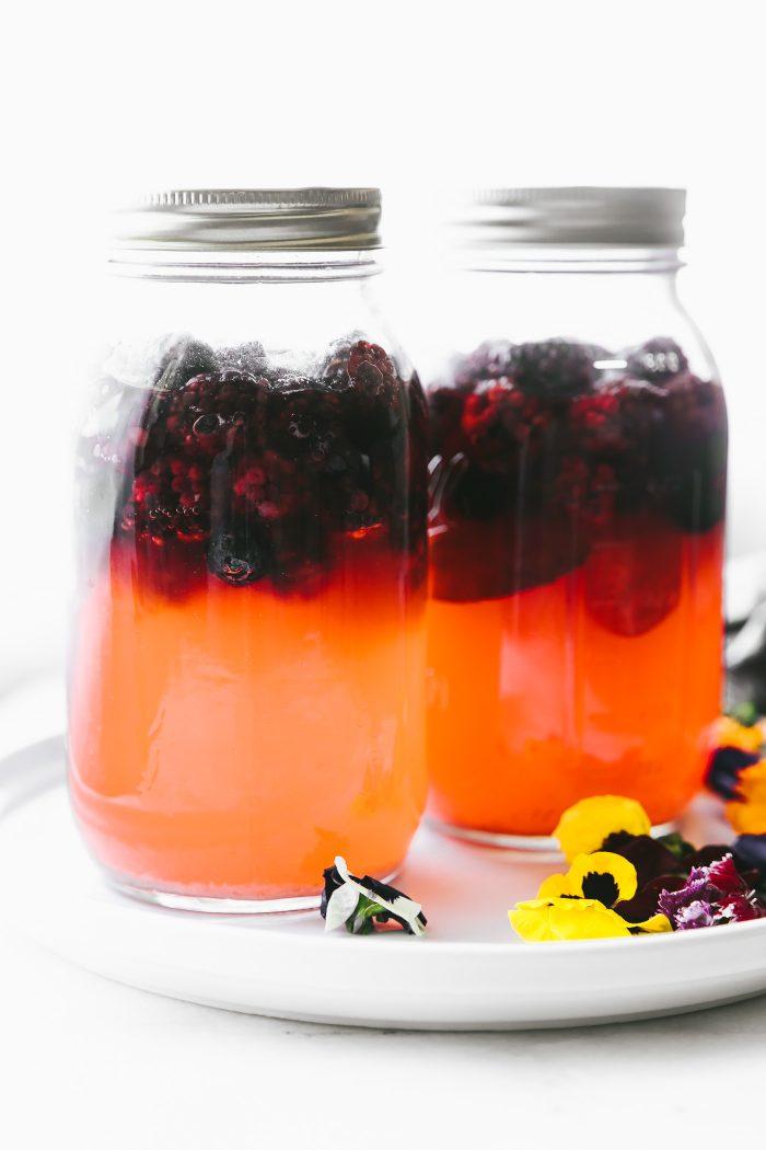 2 quart sized mason jars of kvass with fruit