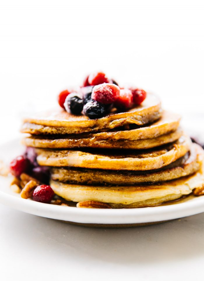stack of coconut flour pancakes topped with fresh berries