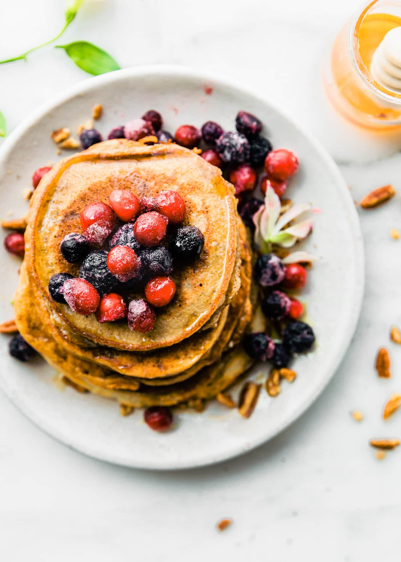 stack of grain free pancakes topped with cranberries and blueberries