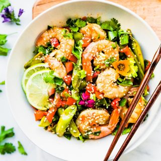 wok fired orange shrimp stir fry recipe! It's full of fresh, snappy Asian flavors and made all in one pan! Shrimp, bell peppers, and snap peas are coated in a delicious spicy honey orange sauce.  Gluten free, Whole 30 friendly, and can be adapted for a paleo version.