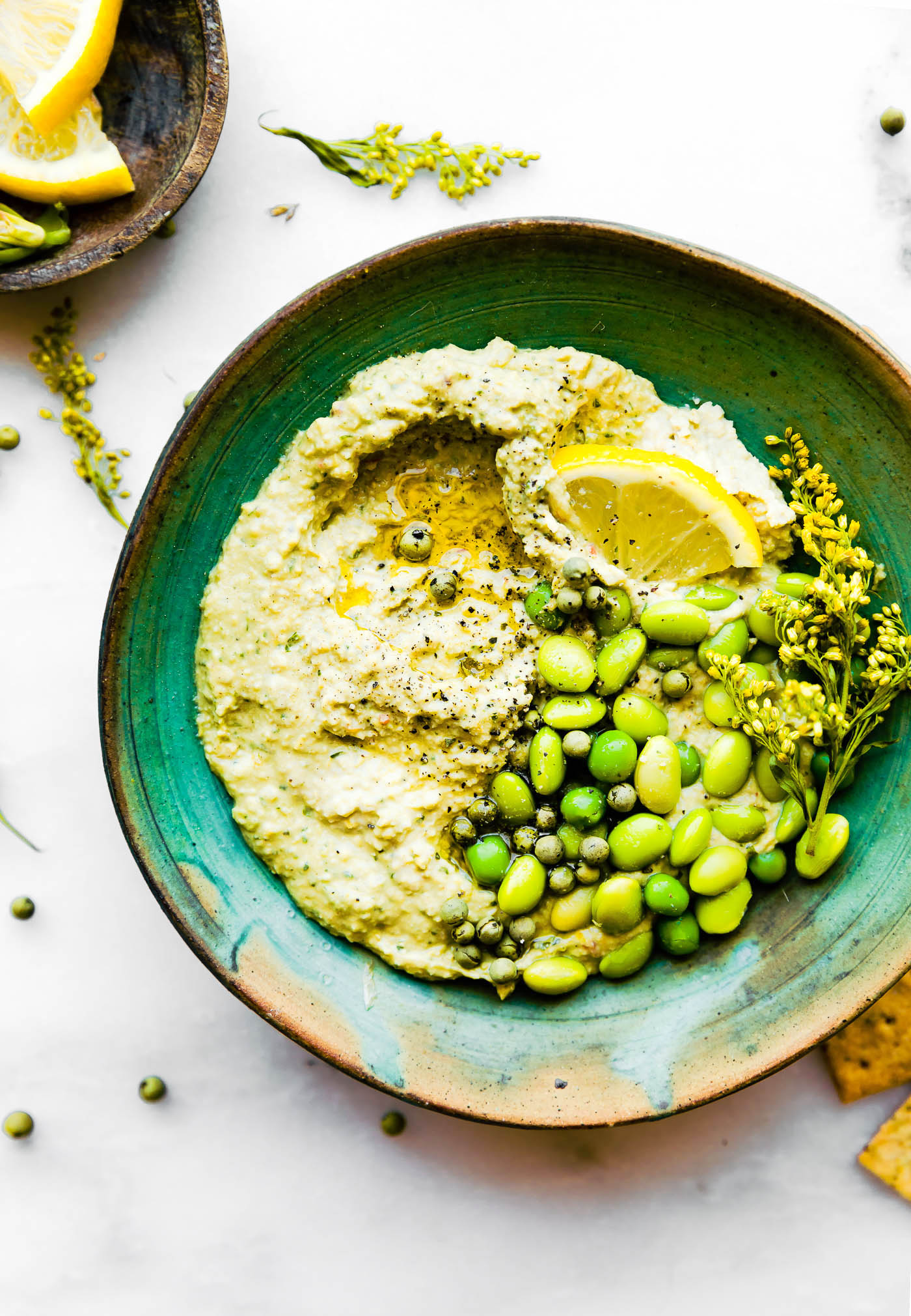Quick Vegan Edamame Pesto dip! A vegan pesto dip recipe that creamy, healthy, and flavorful.  Nut free, rich in plant protein, and made with less than 6 ingredients. Use this edamame pesto dip on a sandwiches, in pasta, or make into wholesome appetizer dip.
