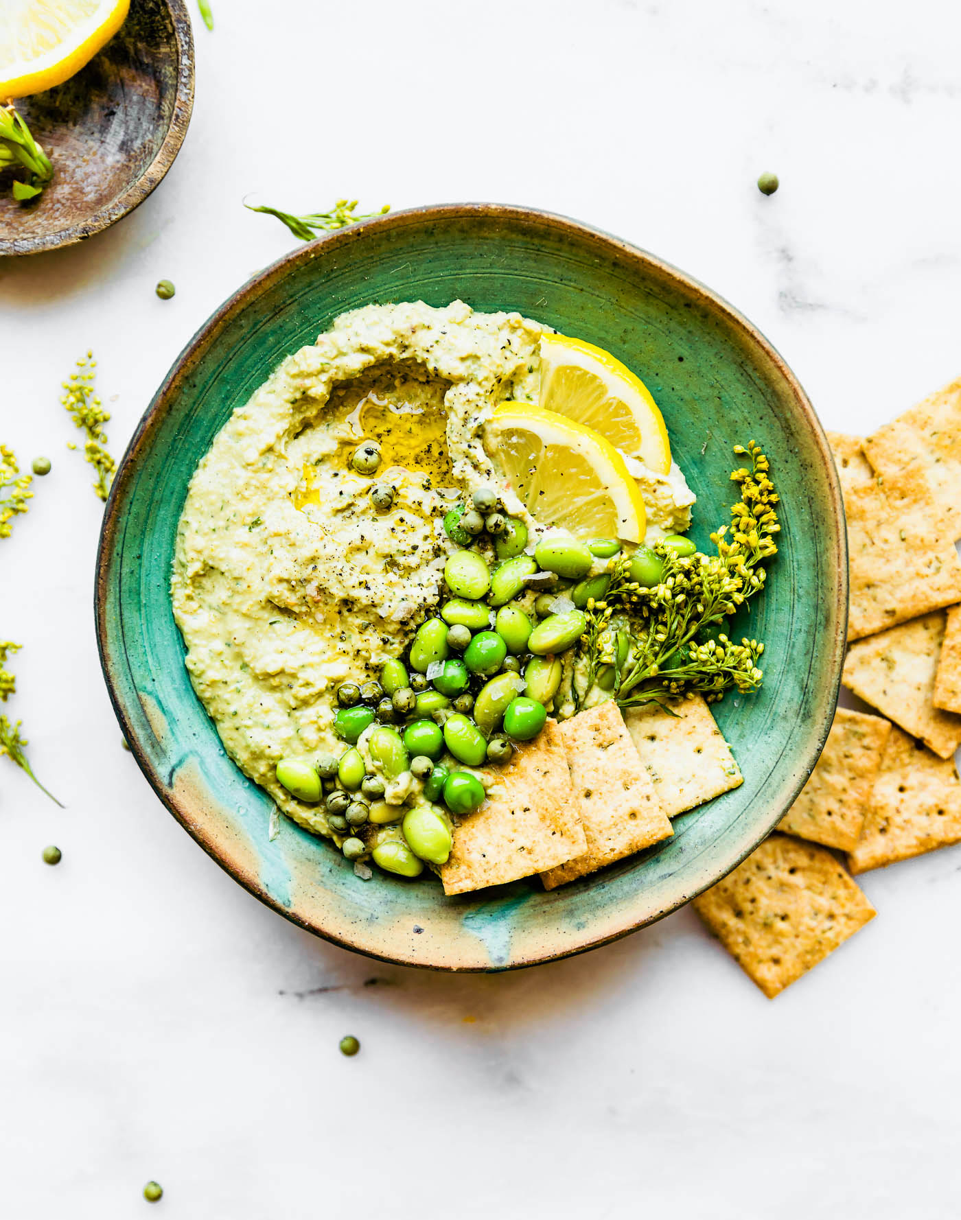 Quick Vegan Edamame Pesto dip! A vegan pesto dip recipe that creamy, healthy, and flavorful.  Nut free, rich in plant protein, and made with less than 6 ingredients. Use this edamame pesto dip on a sandwiches, in pasta, or make into wholesome appetizer dip. #dip #pesto #vegan #healthy #appetizer #snack #dairyfree