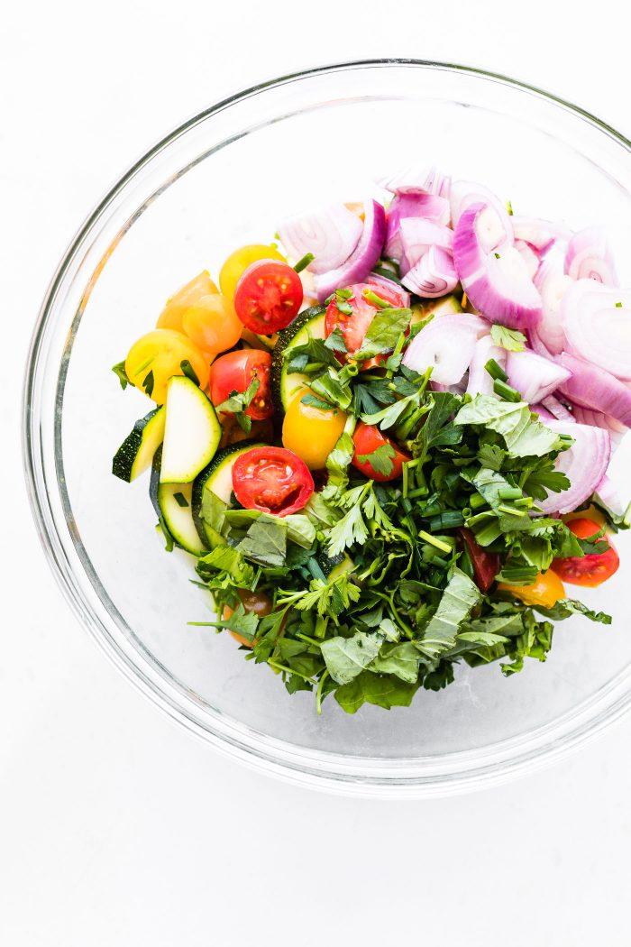 Overhead image of zucchini tomato salad in a bowl